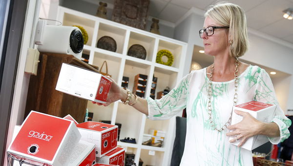 Becky Youngblood sets out merchandise in a display at the downtown retail and clothing store Allez-Oup.  Local retailers are already making plans — and orders — ahead of the upcoming holiday shopping season. (Alaina Denean | Times-Journal)