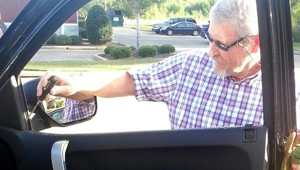 Florida resident Marshall Carroll begins the process of cleaning out glass from inside his truck Friday morning. Carroll and his wife stayed at the Holiday Inn Express Thursday evening and found their truck was one of seven cars vandalized in the parking lot overnight. (Alaina Denean | Times-Journal)