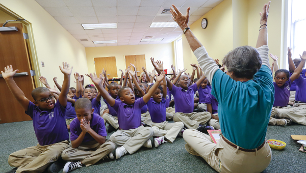 Selma-Dallas County Public Library director Becky Nichols teaches hand motions to the Clark Elementary School first graders. The first graders attended the 'Welcome To Your Library' campaign where they all received their own library card.  -- Alaina Denean