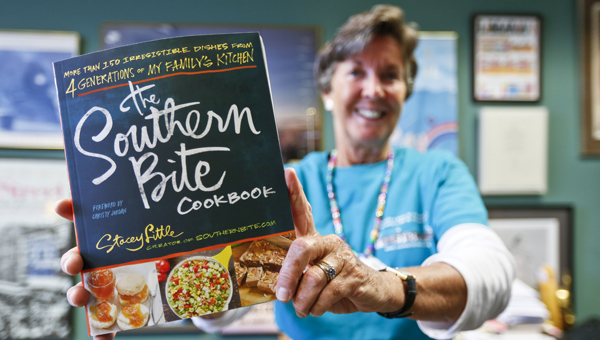 """Selma-Dallas County Public Library director Becky Nichols holds up """"The Southern Bite"""" cookbook.  The cookbook's author, Stacey Little, will be the featured speaker at the next Lunch at the Library event set for Thursday, Oct. 2. -- Alaina Denean"""