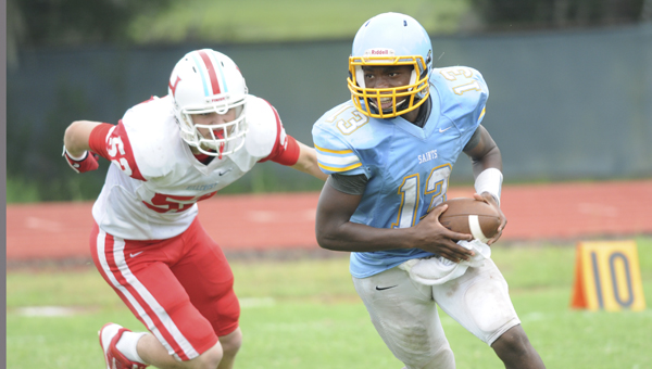 Selma High School quarterback Marquell Moorer tries to run away from a player from Hillcrest-Tuscaloosa in Saturday's game at Memorial Stadium.  Hillcrest won the game 29-26.  The game started Friday night but was suspended due to lightning.--Daniel Evans
