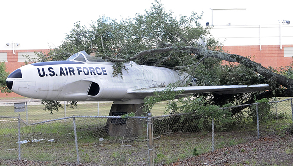 A tree limb lays across the T-33 positioned outside Selma's Memorial Stadium Tuesday.  City crews began removing the limb Tuesday afternoon, discovering significant damage to the plane's cockpit.  Selma's Parks and Recreation Department paid for the plane to be refurbished in May 2011. -- Daniel Evans