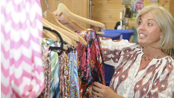 Angie Yeargan sorts out clothing on a rack at Yeargan Farms' Country Store last week. The store is getting ready for Halloween with a new line of products. (Daniel Evans | Times-Journal)