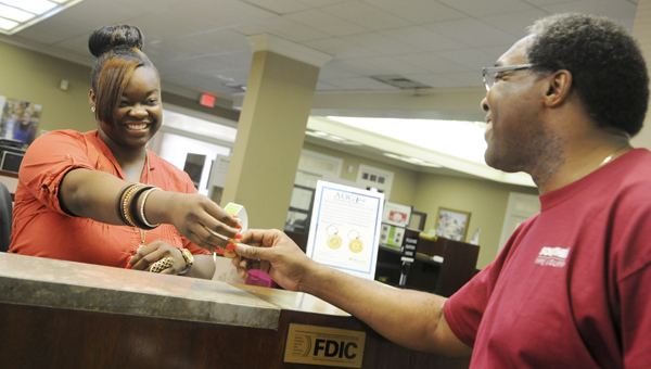 Regions Bank employee Chasmine Alexander, left, hands local resident Donald Jefferson a collegiate keychain Friday. The bank is giving keychains to those willing to donate at least $15 to Selma's Alzheimer's Outreach Group.--Sarah Robinson