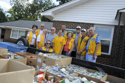 Selma Lions Club pose for the camera Wednesday in front of a trailer full of canned goods they donated to the Christian Outreach Alliance.