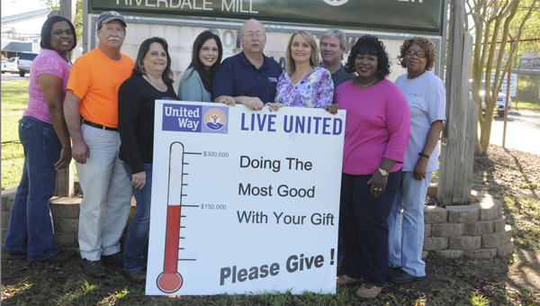 Jeff Cothran, middle, the executive director of the United Way's local chapter, stands among International Paper employees outside of their company building Thursday.  IP donated more than $150,000 to the nonprofit organization's annual fall campaign. --Sarah Robinson