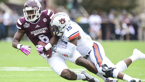 Auburn defensive back Joshua Holsey tackles Mississippi State's Malcolm Johnson during Saturday's game in Starkville. The Bulldogs pulled the upset, beating the Tigers for their straight win over a top-10 ranked team. --Wade Rackley | Auburn University