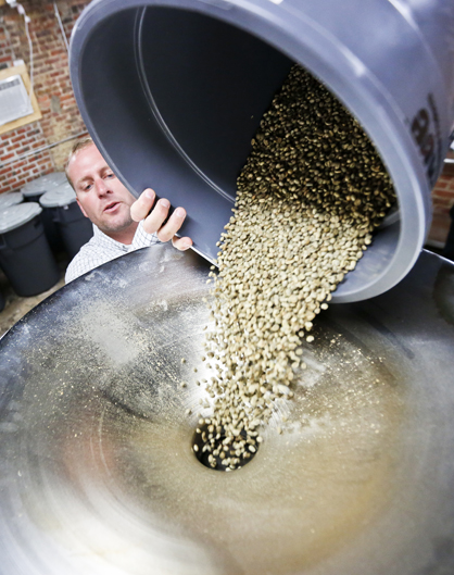 Ryan Bergeron is shown and below dumping beans into the roaster.