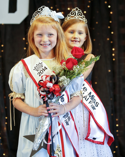 Right, the 2014 Little Miss Central Alabama Fair Kenlee Aldridge Swanson is crowned by last year's queen Emily Boswell.