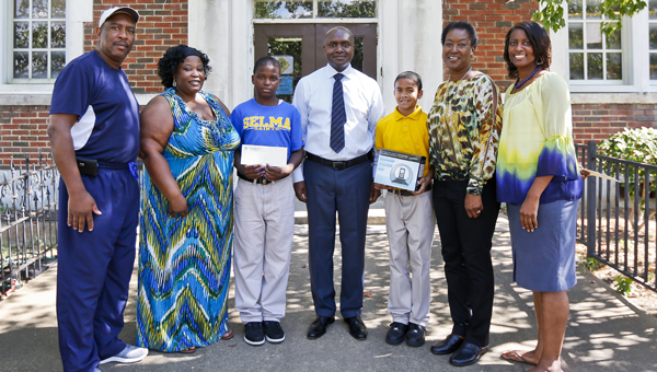 From left, Michael Johnson, Lytasha Smith, Corey Smith Jr., Major W. Burrell, Michael Evans Jr.,  Aurelia Evans Craig and Kesia Smith pose for a photo in front of the School of Discovery.  Smith and Evans Jr. were chosen at random for their perfect attendance and awarded prizes for their dedication to school.--Alaina Denean