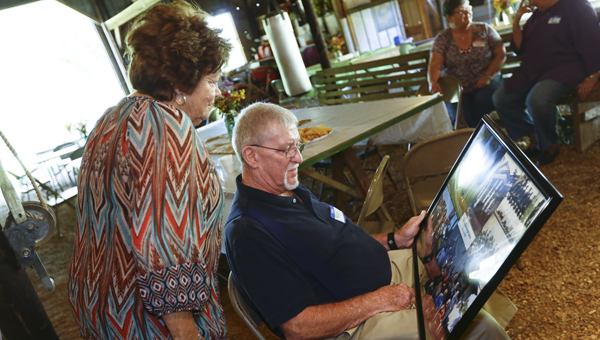 Dallas County High School alums Judy Tucker Harris and Roy Abbott reminisce and look at photos of their class during a reunion Tuesday near Plantersville.