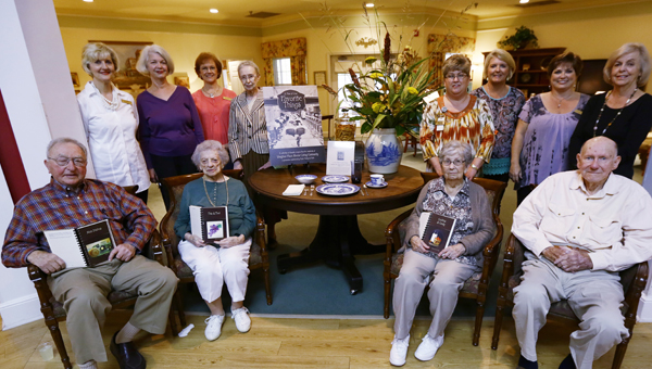Vaughan Place Senior Living Community residents, staff and volunteers pose for a picture with their cookbook. (Alaina Denean   Times-Journal)