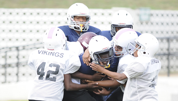 Bears running back Santrez White runs in an Selma youth league Opening Day game against the Vikings. The price and availability of helmets kept as many as 150 kids from playing youth football this fall, according to football director Terry Jackson.