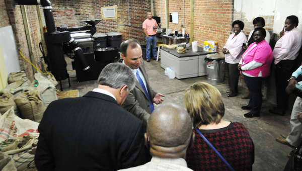 Ryan Bergeron from Revival Cofffee Company gives a tour of his new business Friday.  Above, Dane Shaw of the Dallas County Fatherhood Initiative shows visitors some green, unroasted coffee beans.