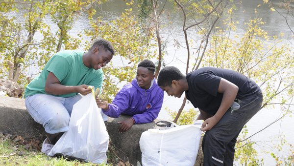 Bulldog Brotherhood members Nathaniel Acomm, Jaelon Williams and Drederrion Harris clean up along Water Avenue on Tuesday morning with the rest of their group. Bulldog Brotherhood is a R.B. Hudson mentoring group that teaches young men life lessons through community service acts.