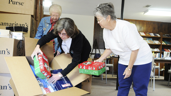 Frances Ingram, left, Relay Center Coordinator Sandra Canterbury, middle, and Susan Jones help load a box full of shoeboxes filled with gifts meant for Operation Christmas Child.--Sarah Robinson