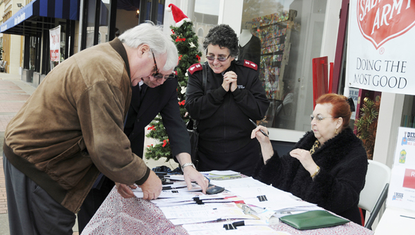 First Cahawba Bank president Catesby Jones, left, collects angels on behalf St. Paul's Episcopal Church and the bank Tuesday at the Angel Tree Blitz, as the Salvation Army's Majors Steve Welch, Mary Welch and board member Jewel Williamson watch.