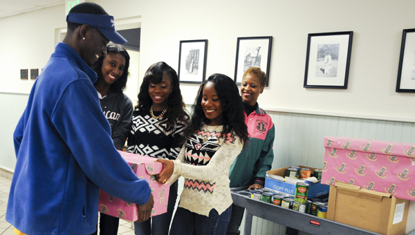 Sarah Robinson | Times-Journal helping hands: Members of the Senior Culturama Club of Alpha Kappa Alpha Sorority Inc.'s Zeta Eta Omega Chapter donate more than 100 canned goods to Reginald Smith, left, with Edmundite Missions' Bosco Food Kitchen, on Tuesday. The club gave to the kitchen, which provides about 1,000 meals daily to the less fortunate, to help fulfill its mission to teach young ladies the importance of giving back
