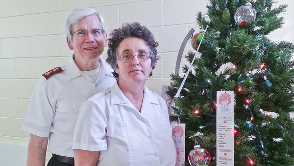 Majors Steve and Mary Welch of Selma's Salvation Army pose for a picture beside a Christmas Angel tree Friday.