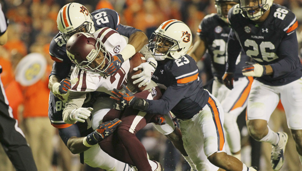 Auburn's Brandon King, middle, and Johnathan Ford, right, tackle Texas A&M's Speedy Noil during Saturday's game.--Alaina Denean