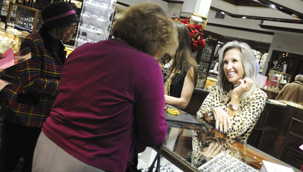 indy Hartzog, a representative with Endless Jewelry, helps shoppers at Butler Truax Jewelers during Monday night's Preview Party in downtown Selma.