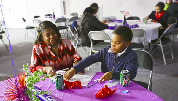 Angela Snell looks on as Ronald Thomas writes on his luminaria during the Relay For Life Selma-Dallas County kickoff