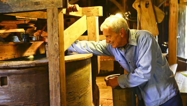 Jim Wood works the stone ground cornmeal Saturday at Kenan's Mill Festival.  Wood was explaining to visitors how to make meal,  while using equipment he said was there in the 1800s.