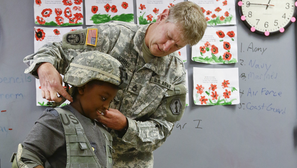 Army veteran Tim Johns helps Valley Grande Elementary third grader George Fails try on military gear.