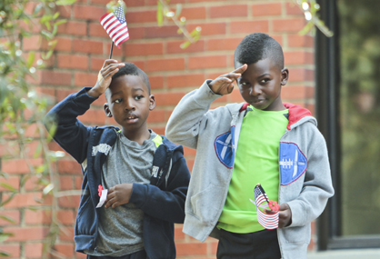 Rashad and Rodney Thomas salute the flag during the Veterans Day program Tuesday at Memorial Stadium in Selma.