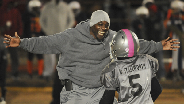 Raiders coach Alvin Barnett runs toward and prepares to hug Markeice Stallworth Jr. after the Raiders defeated the Dolphins to win the 7, 8, 9 and 10-year-old youth football championship game Thursday night at Memorial Stadium. --Daniel Evans