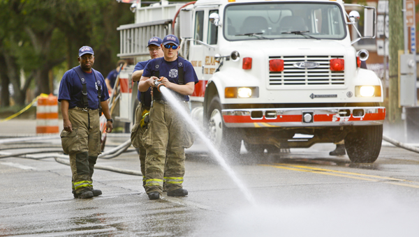 Members of the Selma Fire Department hose down a street Monday morning as clean up from this weekend's activities was in full swing.  Most of the litter was picked up by Tuesday.