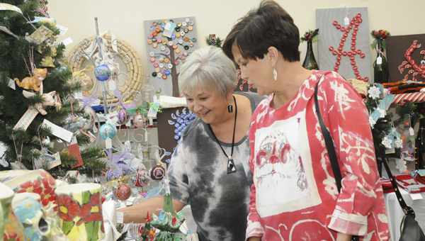 Terri Johnson, left, shows Cheryl Till some of the the unique Christmas decorations made by people in Selma at the Holiday House fundraiser at the Larry D. Striplin Performing Arts Center Monday.