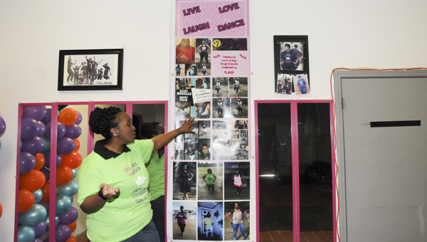 Lashun Langdon looks over photos hanging in her studio chronicling here weight loss journey.