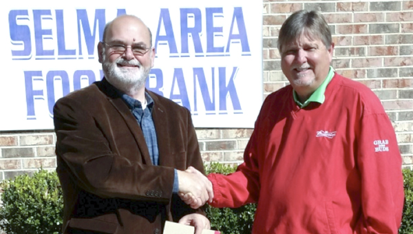 The Selma Area Food Bank executive director Jeff Harrison accepts the building's deed from Steve South, Bama Budweiser Selma general manager.
