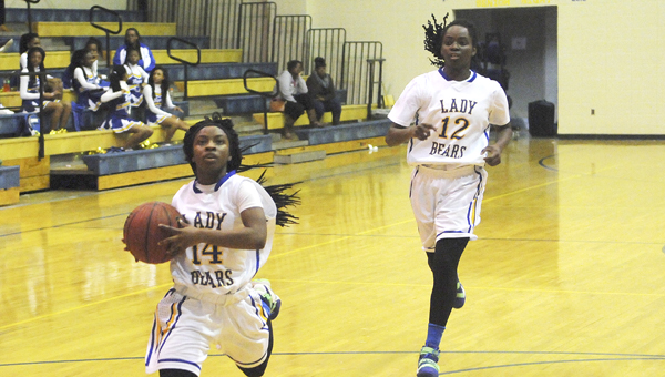 Keith's Ambdreya Snow races up the floor for a layup attempt while Harriet Winchester looks on from behind.  Snow and the Bears forced 27 turnovers and blew out Billingsley 69-21 to move on to the Central Regional in Montgomery on Thursday. --Daniel Evans