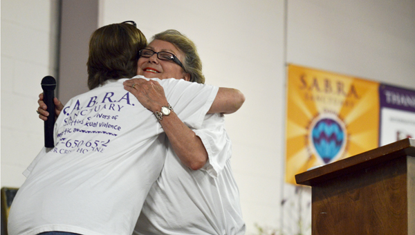 Mae Mae Jackson hugs Nancy Travis after being awarded with The Roy L. Johnson Exemplary Service Award during SABRA's  Sanctuary annual auction Thursday night.