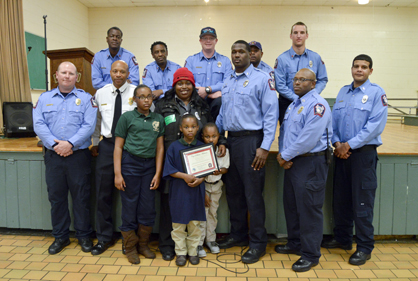 Tamyah Johnson, 8, poses for a photo Wednesday with her family and members of the Selma Fire Department.
