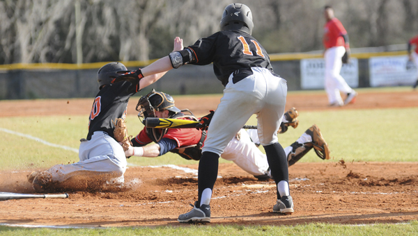 Wallace Community College Selma's Zack Seagle tags Marion Military Institute's Carson McGregory out at home plate during Tuesday's gmae at Bloch Park.  Marion's Logan Nix is in the foreground telling McGregory where to slide into home plate.  Marion scored six runs in the sixth inning and won the game 10-2.--Daniel Evans