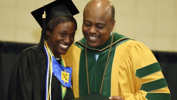Priscilla Lanise Smith and Concordia College Alabama president the Rev. Dr. Tilahun M. Mendedo share a laugh and pose for a photo during the college's graduation ceremony Saturday.