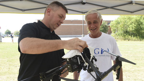 Andy Beck with Viper Imaging shows off a drone to Oscar Wayne Calloway with the Alzheimer's-Autism Outreach Group.