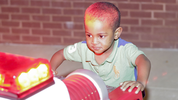 Leon Pettaway plays with the Selma Fire Department's Engine 3.5 Thursday at the city's Crime Night Out.--Alaina Denean Deshazo